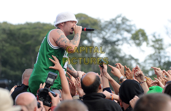 FRED DURST.Limp Biscuit performing at Leeds Festival 2010, Bramham Park, Leeds, England..28th August 2010.stage concert live gig performance music half length celtics green sleeveless top hat white tattoos singing fans crowd audience crowd surfing lifting carrying profile side .CAP/BEL.©Tom Belcher/Capital Pictures.