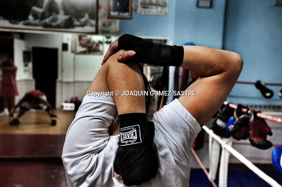 Young amateur boxer Maria doing stretches during a training day at the boxing club Martinez