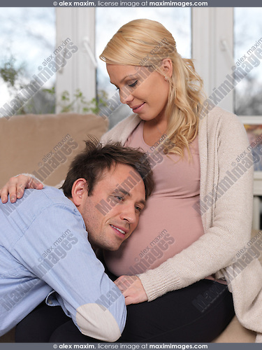 Happy future parents. Husband listening to a baby moving inside his 9 month pregnant wife's belly.