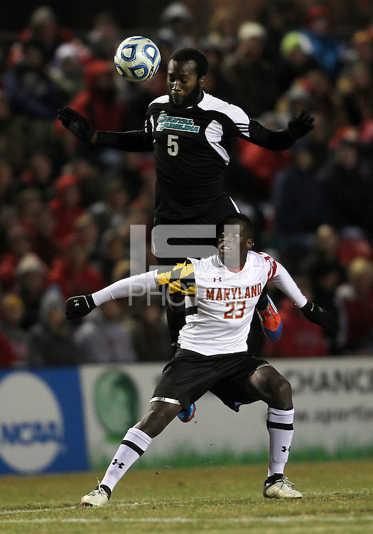 COLLEGE PARK, MD - NOVEMBER 25, 2012: Schillo Tshuma (23) of the University of Maryland looses a high ball to Jhamie Hyde (5) of Coastal Carolina University during an NCAA championship third round match at Ludwig Field, in College Park, MD, on November 25. Maryland won 5-1.