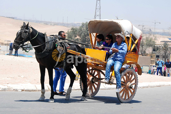 Egyptians ride a horse cart in front of the Giza pyramids, on the third day of Eid al-Fitr holiday which marks the end of the Muslim holy month of Ramadan, in Cairo on July 19, 2015. Photo by Amr Sayed