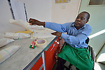 Sunny Nyamandwe folds and packages bandages as part of his work at the National Rehabilitation Centre in Ruwa, Zimbabwe. The Centre assembles and fits wheelchairs provided by the Jairos Jiri Association with support from CBM-US, and Nyamandwe is one of the beneficiaries of the program. His legs remain paralyzed after an automobile accident more than two decades ago.