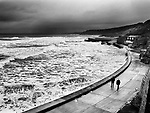 People Walking by the Sea Wall in Bad Weather at High Tide in South Bay at Scarborough North Yorkshire England