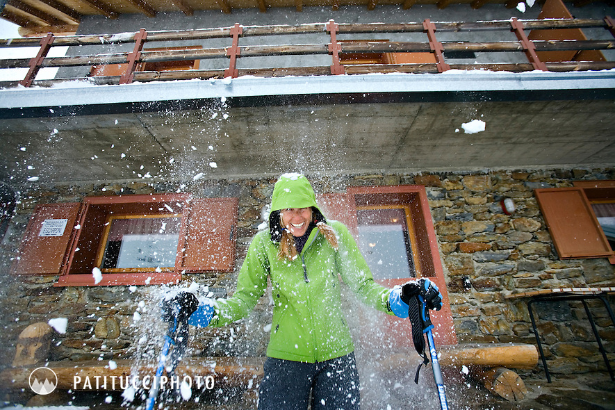 Amy Rasic getting hit by falling snow from roof top while on a ski tour of the Ortler area of northern Italy