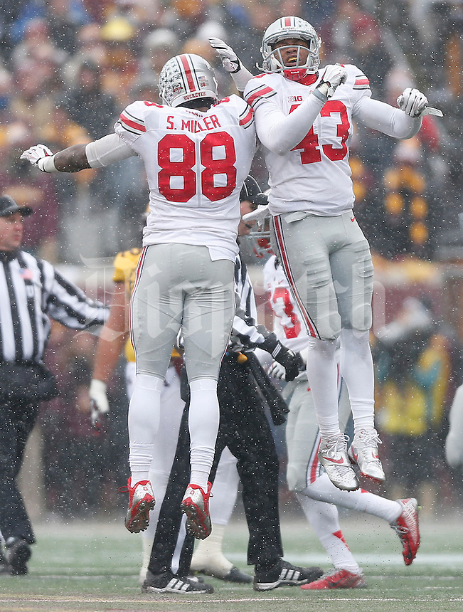 Ohio State Buckeyes defensive lineman Steve Miller (88) and Ohio State Buckeyes linebacker Darron Lee (43) celebrate after a defensive stop during the college football game between the Ohio State Buckeyes and the Minnesota Golden Gophers at TCF Bank Stadium in Minneapolis, Saturday morning, November 15, 2014. The Ohio State Buckeyes defeated the Minnesota Golden Gophers 31 - 24. (The Columbus Dispatch / Eamon Queeney)