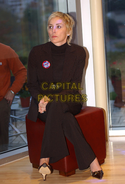 SHARON STONE .Speaks at a John Kerry/John Edwards reception held at the home of Peter Karlovich and Steven Herforth in Mt. Washington. .October 14th, 2004.full length, sitting, legs crossed, hands clasped, brown pinstripes suit.www.capitalpictures.com.sales@capitalpictures.com.© Capital Pictures.