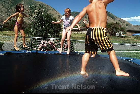 Kids jumping on a trampoline with a sprinkler underneath, causing a rainbow effect.<br />