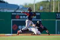 State College Spikes shortstop Luis Flores (16) throws to first base as Harrison Dinicola (24) slides in during a NY-Penn League game against the Batavia Muckdogs on July 1, 2019 at Dwyer Stadium in Batavia, New York.  Batavia defeated State College 5-4.  (Mike Janes/Four Seam Images)