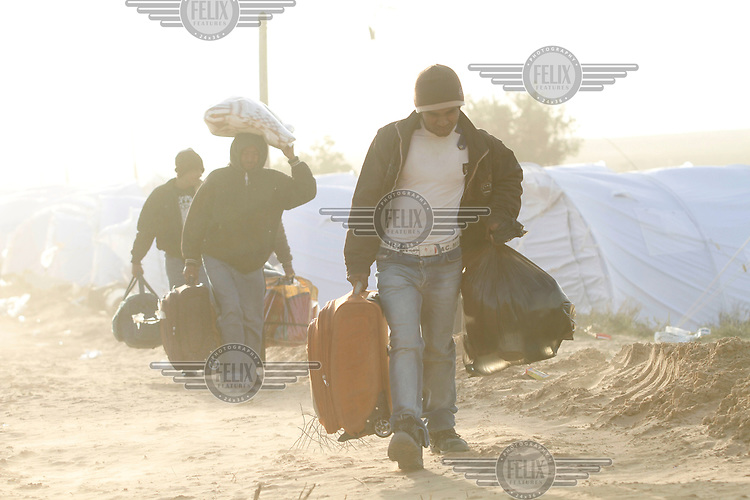 Refugees carry their belongings in at ent camp set up by UNHCR inside the Tunisian border. Tens of thousands of people, mainly migrant workers, fled unrest in Libya and crossed the border into Tunisia. Some slept in the open for several days before being processed.  At the same time forces loyal to Col. Gaddafi fought opposition forces in various parts of the country.
