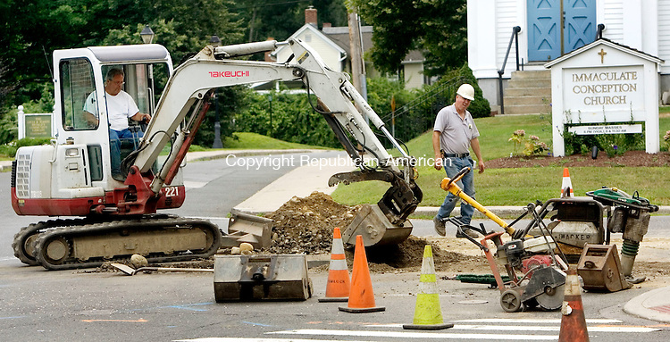 NEW HARTFORD CT. 28 July 2014-072814SV03-Workers from Hemlock Construction Company of Torrington work on a sewer line on Main Street in New Hartford Monday.  The Water Pollution Control Authority has decided to abandon the old clay pipe that burst two weekends ago and divert the waste through a different pipe. The waste will go through a pipe under Central Avenue instead of Bridge Street. The WPCA agreed to spend up to $57,000 for the project.<br /> Steven Valenti Republican-American