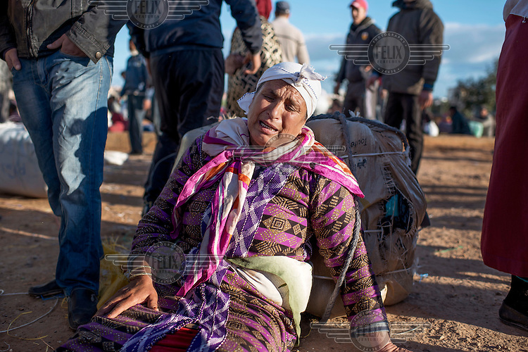 A female porter sits on the ground crying after being crushed during a stampede as hundreds of porters sought to get first in line to cross the Moroccan-Spanish border. Hundreds of people work ferrying heavy loads of imported goods on their backs over the border. Melilla is a Spanish exclave on the north coast of Africa bounded by Morocco and the Mediterranean Sea. Many would-be migrants see it as the gateway to Europe which accounts for the high-level of security along its borders. However, it is also a route of entry for goods and, if they can be carried by a person (the Bario Chino gate is for pedestrians only), do not attract import taxes. Thus a micro-industry has evolved carrying huge packages of goods over the border. Once the preserve of poor women, known as 'Mule-Women', the economic crisis means more and more men are acting as porters and they aggressively seek out the limited employment opportunities.
