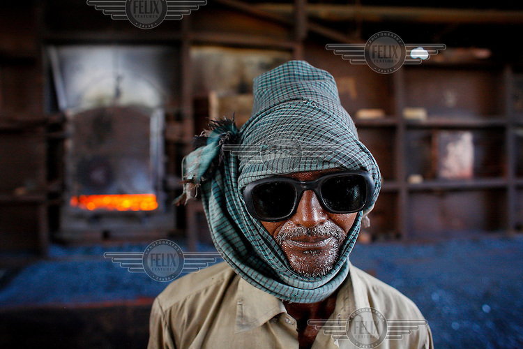 In absence of safety equipment a man handling red hot steel at a steel recycling and re-rolling mill has wrapped his head with a cotton scarve in order to add some miniscule measure of extra protection.
