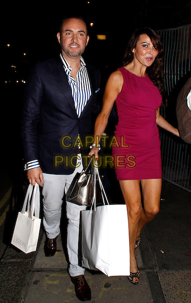 Nick Ede and Lizzie Cundy.Dannii Minogue and Tabitha Somerset Webb launch the Spring Summer 2012 collection of 'Project D' at Mortons, London, England..September 15th, 2011.full length black suit jacket grey gray trousers pink dress goody bags mouth open funny.CAP/COA/CC.©CC/COA/Capital .