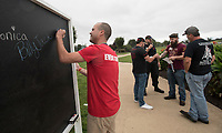 NWA Democrat-Gazette/SPENCER TIREY     Brent Callis places the name of his boss Pam Brock, brother's Larry Anderson, on a chalkboard, Sunday, Sept. 9, 2018, where those walking in the NWA Out of Darkness Walk can place names of people they are walking in memory of in Orchard Park. Hundreds of people walked in the 5th annual walk  support of the American Foundation for Suicide Preventing supporting the goal to reduce the annual suicide rate 20 percent by 2025.