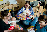 "A mother breastfeeds her baby at a drop-in breastfeeding support centre while talking to another mother and the breastfeeding consultant.<br /> <br /> Image from the ""We Do It In Public"" documentary photography project collection: <br />  www.breastfeedinginpublic.co.uk<br /> <br /> Dorset, England, UK<br /> 17/04/2013"