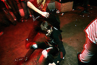 A concert-goer gets help getting up after falling in the middle of a mosh pit during a concert in the basement of the White House in Woodstock, Illinois.  The White House was a small suburban residential home rented by a group of 20-somethings in Woodstock, Illinois, a distant northwestern suburb of Chicago.  For about a year, the renters of the house staged punk-rock concerts in the house's small basement, without the approval of the neighborhood, local government, or police.  .