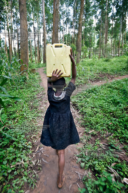 Nine year old Robinah walks into the forest to fetch water.
