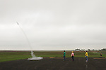CHAD PILSTER &bull;&nbsp;Hays Daily News<br /> <br /> (left to right) Kwinter Hartsthorn, 17, Bison, launches his rocket as Dennis Elder, Bison, the coordinator of the event, Phillip Scheuerman, Bison, and Xander Palmberg, 9, watch on Saturday, August 3, 2013, during the 4-H and Open Class Rocket launch as part of the Rush County Fair at the Rush County Airport in La Crosse, Kansas.