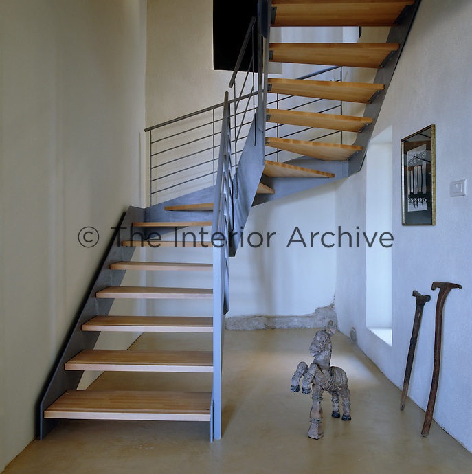 A modern industrial metal and wood staircase ascends to the upper floors of the house