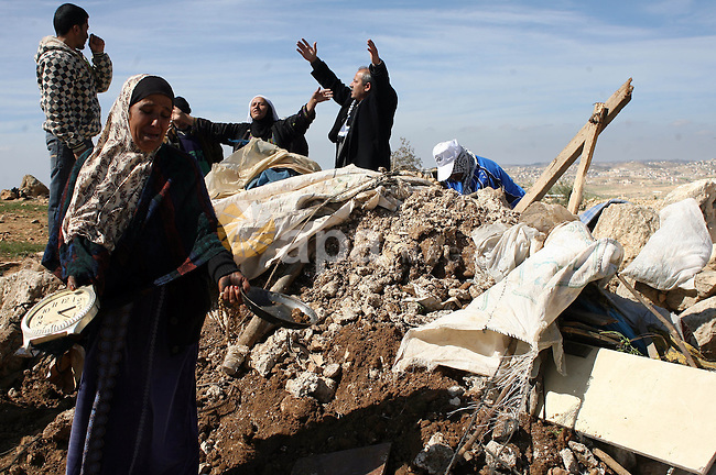 A Palestinian woman weeps as she and her family try to retrieve items from the rubble of his family house after it was destroyed by Israeli army tractors early on 22 February 2011 in the West Bank village of Yatta near Hebron. The house was located in the so-called Area C, a closed military zone where Israel exercises full control and was built without permission, according to the Israeli army. Photo by Najeh Hashlamoun
