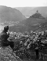 This old castle perched on a hilltop above the Moselle River and the town of Cochem, Germany, is headquarters of the U.S. Fourth Army Corps.  In foreground is Cpl. James C. Sulzer, Fourth Army Corps, Photo Unit.  January 9, 1919.  Sgt. Charles E. Mace. (Army)<br />