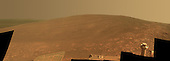 """This scene shows the """"Murray Ridge"""" portion of the western rim of Endeavour Crater on Mars. The ridge is the NASA's Mars Exploration Rover Opportunity's work area for the rover's sixth Martian winter.<br /> The ridge rises about 130 feet (40 meters) above the surrounding plain, between """"Solander Point"""" at the north end of the ridge and """"Cape Tribulation,"""" beyond Murray Ridge to the south. This view does not show the entire ridge. The visible ridge line is about 10 meters (33 feet) above the rover's location when the component images were taken. The scene sweeps from east to south. The planar rocks in the foreground at the base of the hill are part of a layer of rocks laid down around the margins of the crater rim. At this location, Opportunity is sitting at the contact between the Meridiani Planum sandstone plains and the rocks of the Endeavour Crater rim. On the upper left, the view is directed about 22 kilometers (14 miles) across the center of Endeavour crater to the eastern rim. Opportunity landed on Mars in January 2004 and has been investigating parts of Endeavour's western rim since August 2011. The scene combines several images taken by the panoramic camera (Pancam) on NASA's Mars Exploration Rover Opportunity during the 3,446th Martian day, or sol, of the mission's work on Mars (Oct. 3, 2013) and the following three sols. On Sol 3451 (Oct. 8, 2013), Opportunity began climbing the ridge. The slope offers outcrops that contain clay minerals detected from orbit and also gives the rover a northward tilt that provides a solar-energy advantage during the Martian southern hemisphere's autumn and winter. The rover team chose to call this feature Murray Ridge in tribute to Bruce Murray (1931-2013), an influential advocate for planetary exploration who was a member of the science teams for NASA's earliest missions to Mars and later served as director of NASA's Jet Propulsion Laboratory, in Pasadena.<br /> This view is presented in approximately true color, merging ex"""