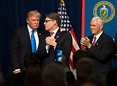 United States President Donald J. Trump (L) embraces Energy Secretary Rick Perry as Vice President Mike Pence applauds (R), after Trump delivered remarks on at the Unleashing American Energy event at the Department of Energy in Washington, D.C. on June 29, 2017. Trump announced a number on initiatives including his Administration's plan on rolling back regulations on energy production and development. <br /> Credit: Kevin Dietsch / Pool via CNP