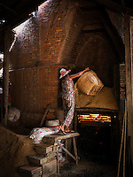"This 65 year old lady feeding the traditional Brick Kiln with rice husks near Can Tho, the hub of the Mekong Delta (Vietnamese: Đồng bằng Sông Cửu Long ""Nine Dragon river delta""), also known as the Western Region (Vietnamese: Miền Tây or the South-western region (Vietnamese: Tây Nam Bộ) is the region in southwestern Vietnam where the Mekong River approaches and empties into the sea through a network of distributaries. The Mekong delta region encompasses a large portion of southwestern Vietnam of 39,000 square kilometres (15,000 sq mi). The size of the area covered by water depends on the season.<br />