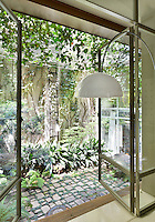 A full height glass door leads to a garden beyond. Just seen in front of the door is the white shade of a contemporary floor lamp