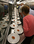 Passengers on a galley tour aboard the Queen Mary 2 as they walk pass long lines of prepared plates for lunch in the many restaurants offered on ship.