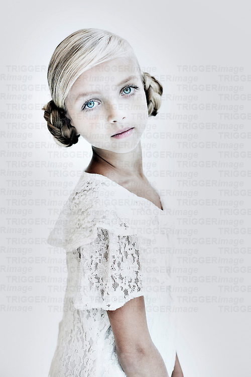 Female youth wih plaited hair looking at camera wearing white lace dress