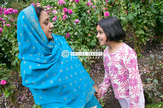 Young girl and mother talking to each other in the garden,