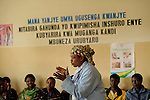 In the Gisenyi community hospital in Rwanda, hygienist  Desange Mukasine gives a maternal health talk to a room full of pregnant women, and a few expecting fathers...wall reads:  .May God Listen To My Prayers..I come for prenatal services and family planning four times before giving birth at the hospital.