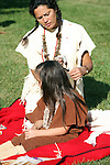 A Native American Indian woman braiding a young childs hair