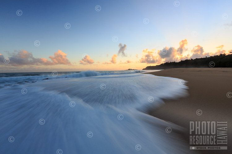 Just before sunrise, white wash rushes onto shore at Secrets (or Secret) Beach, North Kaua'i.