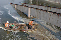 Workers collect rubbish from the polluted water in the second ring canal in Beijing, China. The local government has recently worked out a plan to bring the canal pollution under control within 10 years. .10 Jul 2007