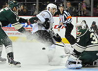 San Antonio Rampage center Wade Megan, center, takes a shot on Iowa Wild goaltender John Curry, right, as Iowa defenseman Kyle Medvec closes in, during the second period of an AHL hockey game, Saturday, Jan. 25, 2014, in San Antonio (Darren Abate/AHL)