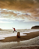 USA, Washington State, man jumping off of a tree stump at Rialto Beach, Olympic National Park