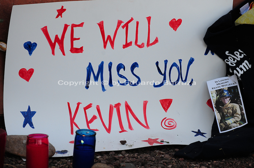 "Phoenix, Arizona. July 3, 2013. A small makeshift memorial for the 19 Arizona firefighters who died on June 30 battling the Yarnell Hill wildfire was built outside the Forensic Science Center in Phoenix, where autopsies are being conducted. ""We will miss you Kevin"", reads this sign made to honor Kevin Woyjeck, 21, who is among the 19 victims of the Yarnell Hill wildfire in Arizona. Photo by Eduardo Barraza © 2013"