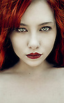 A close up portrait of a girl with red hair and blue eyes, staring straight at the camera..