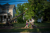 A passerby with a stroller looks over storm damage to a house on North State Street in Westerville, Ohio, three days after a storm felled trees and power lines leaving as many as 1 million people without power in Ohio. This house, occupied and for sale when the storm struck, is still waiting for an insurance adjuster to complete the damage claim although neighbors speculate the damage to be so severe that the house might not be repaired but torn down.
