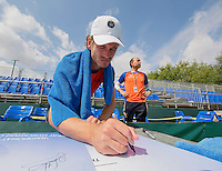 Moscow, Russia, 13 th July, 2016, Tennis,  Davis Cup Russia-Netherlands, Training Dutch team, Wesley Koolhof signing autographes on posters in the background team manager Robert Jan Schumacher<br /> Photo: Henk Koster/tennisimages.com