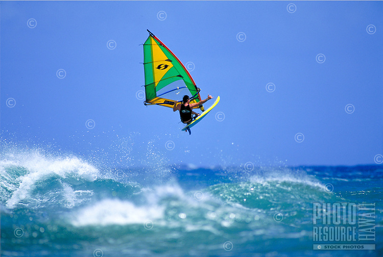 A windsurfer, takes to the air, giving a 'shaka' sign against a clear blue sky.