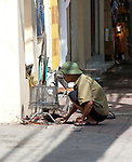 Hanoi, Vietnam, A man in green pith helmet owkrs on his bicycle. photo taken July 2008.