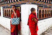 A young Buddhist monk walks past another lama making a phone call at the Tashichhodzong (fortress of auspicious religion) in the capital city Thimphu, Bhutan. Photo: Sanjit Das/Panos