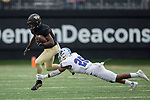 Chuck Wade Jr. (9) of the Wake Forest Demon Deacons tries to avoid the tackle attempt by Ryan Burgess (25) of the Presbyterian Blue Hose during first half action at BB&T Field on August 31, 2017 in Winston-Salem, North Carolina.  (Brian Westerholt/Sports On Film)