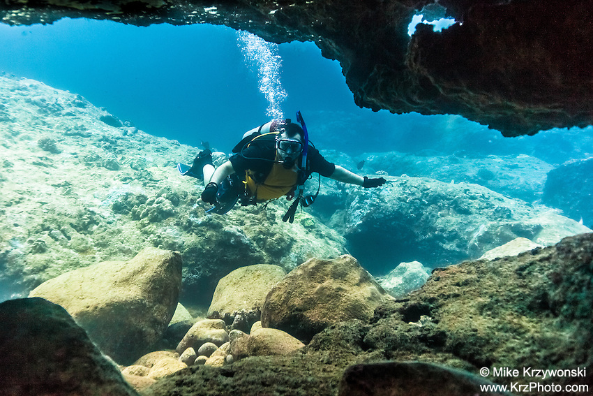 Caucasian male scuba diving in an underwater cave at Shark's Cove, North Shore, Oahu, Hawaii