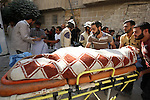 Syrians carry a body of a man following a reported barrel-bomb attack by Syrian government forces, in the Tariq al-Bab neighbourhood in the northern city of Aleppo, on August 21, 2015. Photo by Ameer al-Halbi