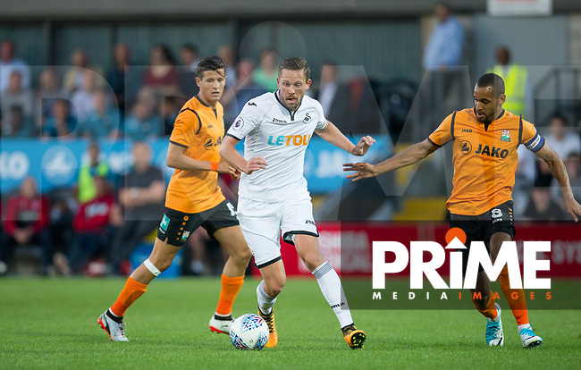 Gylfi Sigurosson of Swansea City holds off Curtis Weston of Barnet during the 2017/18 Pre Season Friendly match between Barnet and Swansea City at The Hive, London, England on 12 July 2017. Photo by Andy Rowland.
