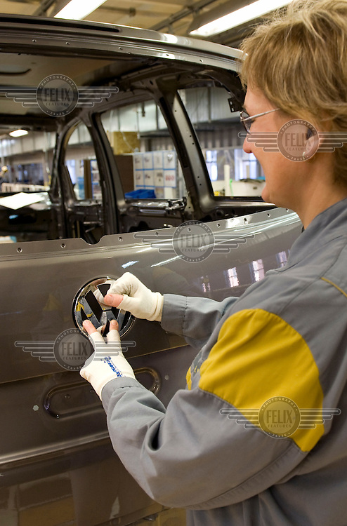 A worker attaches a Volkswagen (VW) logo to a Tiguan model at the car plant Wolfsburg.